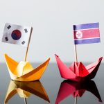 flags of southkorea and northkorea in paper ships